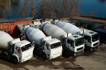 Concrete mixers trucks and construction materials on the parking near the river