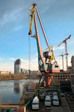 Loading-unloading crane in the river dock of an industrial enterprise. Nearby in the parking lot are three concrete mixer cars. Against the background of the blue sky and the surface of the river.