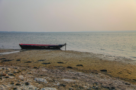 Old lonely fishing boat on the tranquil sea coast