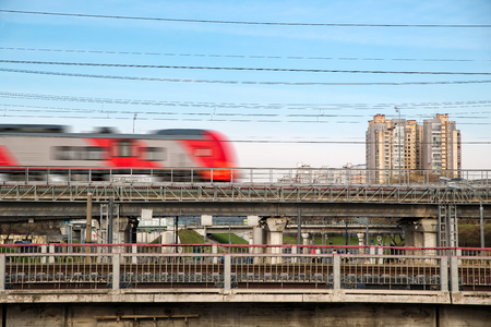Fast modern metro train on the city background. Sunny day with the clear sky. Blurred motion.