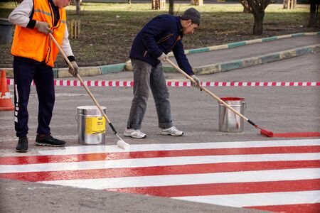 Russia, Moscow, April 12, 2018. Road workers put a red and white strip of road markings on the asphalt for the parking of fire trucks