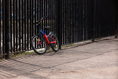 A teenage bike is tied to the fence of the schoolyard on a sunny day in spring and summer. Side view