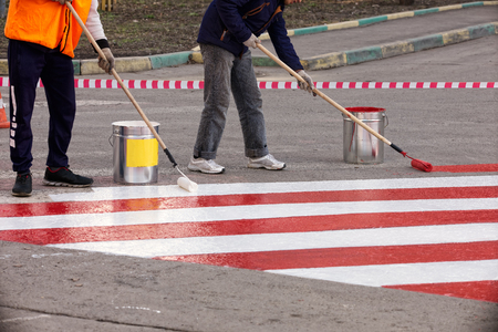 Road workers put a red and white strip of road markings on the asphalt for the parking of fire trucks Banque d'images