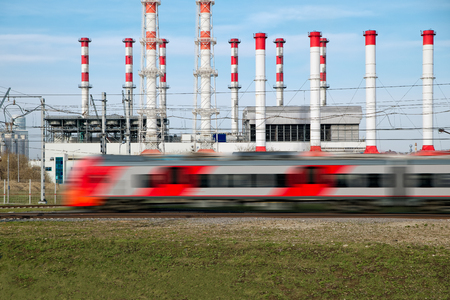 Fast modern metro train behind electrical power station and stack-furnaces. Sunny day with the clear sky. Blurred motion Banque d'images