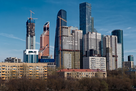 View on group of modern high-rise buildings with old last century buildings in the foreground. Blue sky. Moscow, Russia Banque d'images