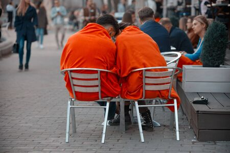 Russia, Moscow, April 15, 2018. A pair of lovers - a man and a woman, covered with orange blankets, sit on a bench near a summer cafe in the Gorky Park looking into mobile phone screen. Éditoriale
