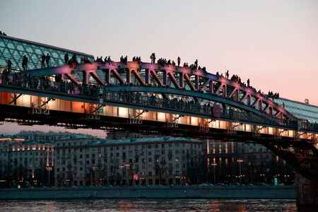 Russia, Moscow, April 15, 2018. People have rest on transparent roof of the bridge over Moscor river in spring and summer evenings at sunset. Éditoriale