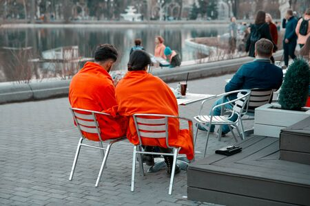 Russia, Moscow, April 15, 2018. A pair of lovers - a man and a woman, covered with orange blankets, sit on a bench near a summer cafe in the Gorky Park. The man looks into mobile phone screen.