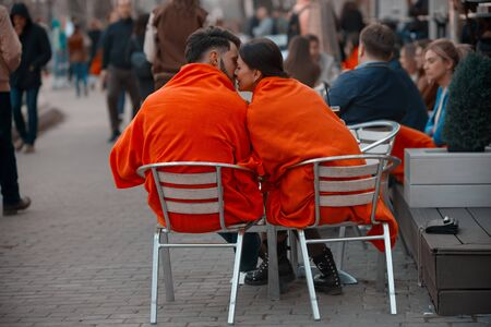 Russia, Moscow, April 15, 2018. A pair of lovers - a man and a woman, covered with orange blankets, kiss on a bench near a summer cafe in the Gorky Park of Culture and Rest Éditoriale