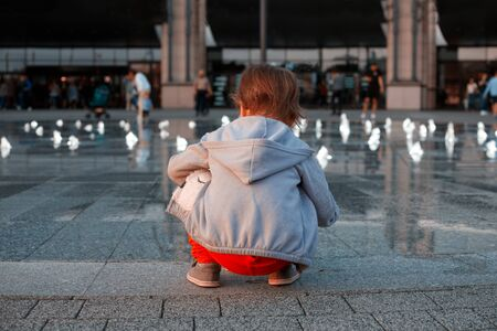 The little girl sits next to the fountain, and plays with the water. Back view. Lifestyle concept Banque d'images