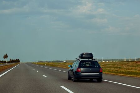 The black car with rooftop cargo carriers is driving along the summer highway on a journey.