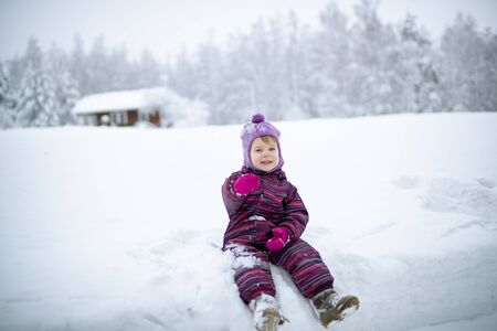 A small girl is sitting on the snow