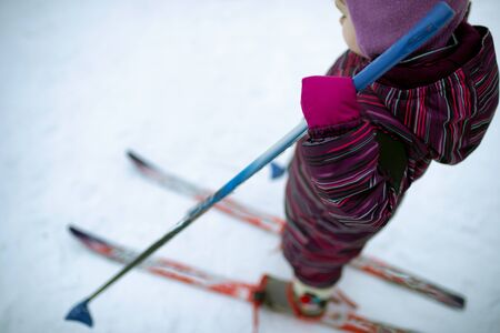 A small girl is skiing on the snow. Daylight. She holds ski poles in her hands. Blur