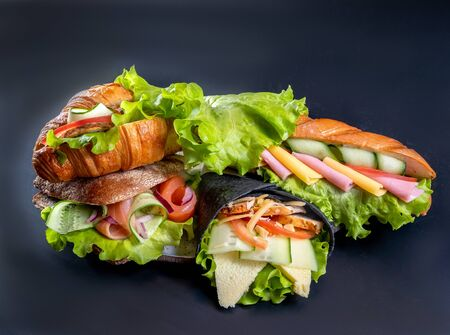 A few sandwiches and rolls with cheese, salad, sausage and vegetables
