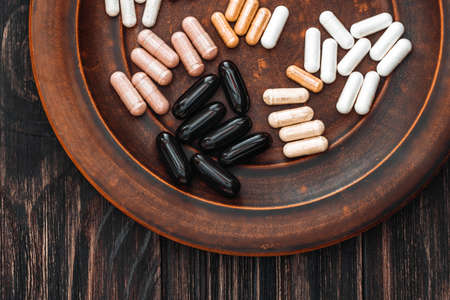 Multivitamin pills on a clay plate, on a vintage wooden table