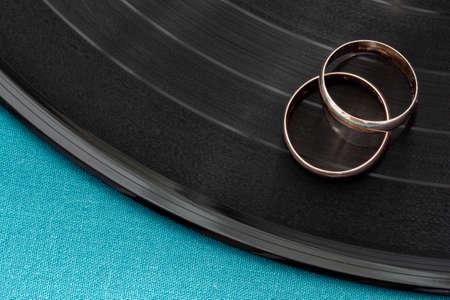 Two gold wedding rings lie on vinyl disc