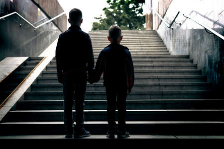 Two boys are standing, holding hands, down on the stairs and looking up, where they have to go now