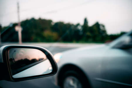 photo of a car rear-view mirror, which reflects the sunset. blurred background. Zdjęcie Seryjne