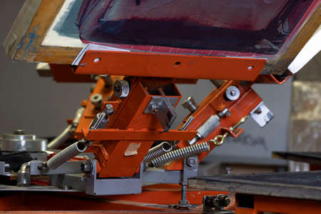 Print screening apparatus. serigraphy production. printing images on t-shirts in a design studio.