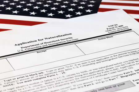 selective focus photo of n-400 form. application for naturalization, on a background of United States flag.