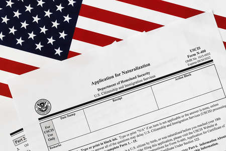 close-up of n-400 form. application for naturalization topview, on a background of United States flag.