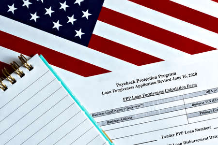 close-up of paycheck protection program loan forgiveness application form revised topview, on a background of United States flag. paycheck protection program new round.