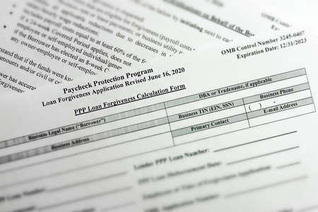 selective focus photo of paycheck protection program loan forgiveness application form revised. paycheck protection program new round