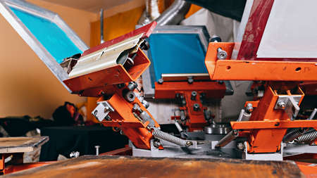 selective focus photo of print screening apparatus. serigraphy production. printing images on t-shirts by silkscreen method in a design studio