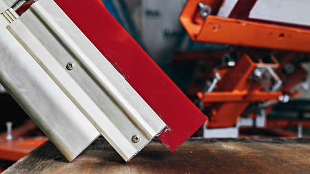 selective focus photo of a squeegee on wooden shelve of the print screening apparatus. serigraphy production. printing images on t-shirts by silkscreen method in a design studio