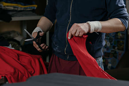 photo of a man with scissors cutting off a piece of red cloth. serigraphy production. printing images on t-shirts by silkscreen method in a design studio