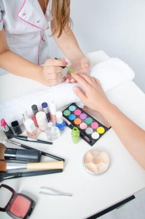 Cosmetologist doing manicure photo