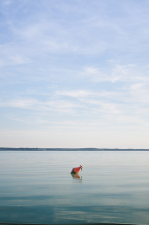 Red buoy floating on the water photo