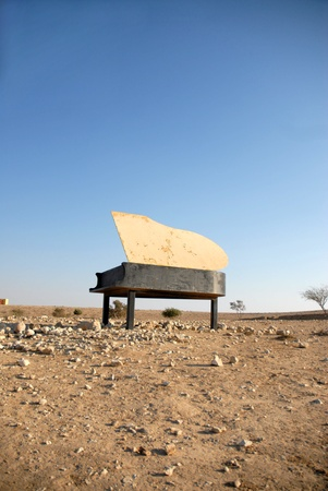 piano in the desert sun by day