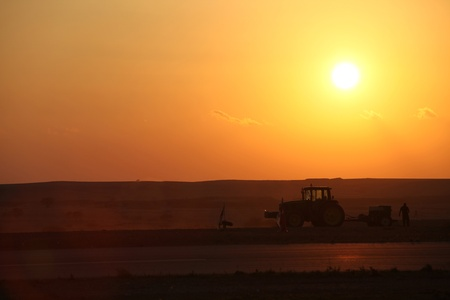 agriculture at sunset hard work, tractor dust soil Stock Photo - 11548404