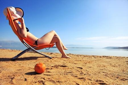 girl sunbathing on the beach with warm summer day photo
