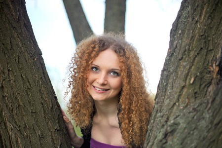 Portrait of a pretty smile girl in the trees