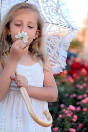 girl with umbrella sniffing a flower photo