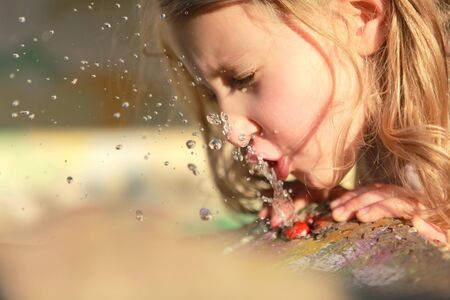 quenching: girl drinks water quenching his thirst