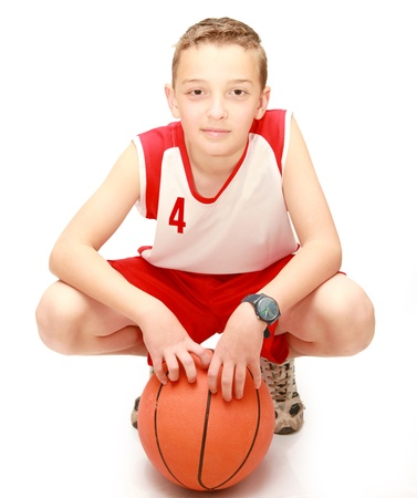 Boy sitting with the ball on the isolated photo