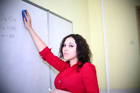 teacher in the red shirt wipes the board photo