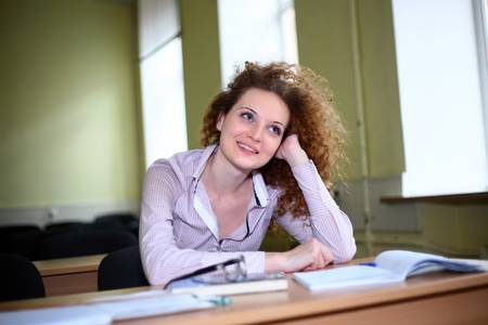 Student girl is sitting at the table photo