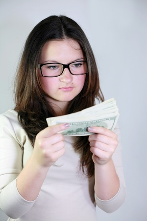 brunette girl considers the money in glasses photo