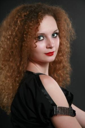 pelirrojas: Retrato de ni�a de rizos en el fondo oscuro