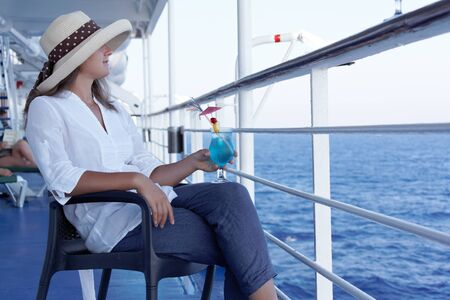 a woman in a hat and a cocktail in the summer on the liner Stock Photo