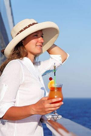 Woman enjoys traveling sipping a cocktail on a summer day Stock Photo