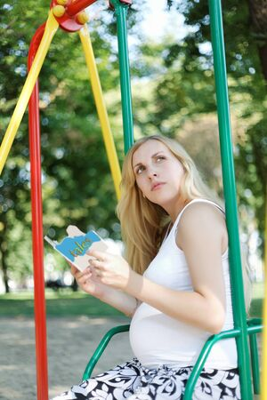 Pregnant girl with a childrens book in park photo