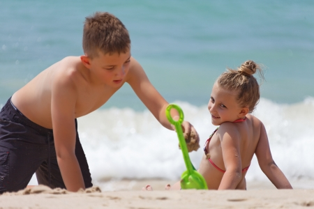 children playing on the beach during the day in the summer photo