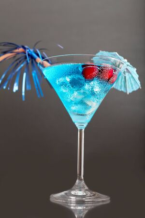 blue hawaiian drink: blue cocktail with ice and umbrella on a gray background Stock Photo