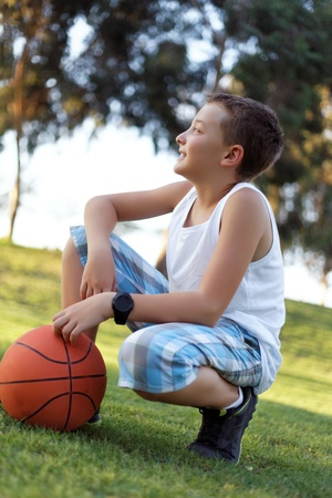 boy with a ball in the fresh air in the park summer photo