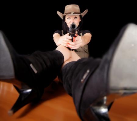 Brunette with a gun dark background